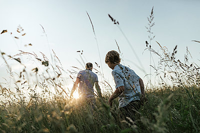 Boy and his father walking in nature at sunset - p300m2005534 by Katharina Mikhrin
