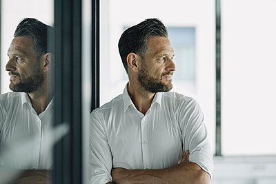Mature businessman leaning against glass wall in office looking sideways - p300m2156385 by Kniel Synnatzschke