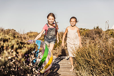 Two happy girls running on boardwalk in dunes - p300m2166953 by Floco Images