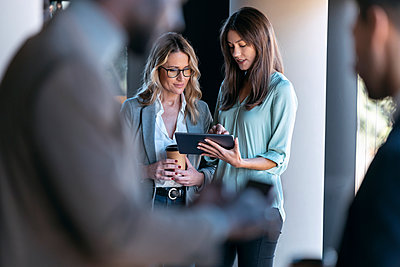 Businesswomen working over digital tablet while standing with colleague in background at office - p300m2256026 by Josep Suria