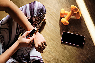 Young woman using smart watch while sitting cross-legged on floor at home - p300m2264773 by Antonio Ovejero Diaz