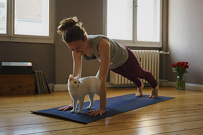 Smiling woman practicing plank position over white cat on exercise mat at home - p301m1579771 by Halfdark
