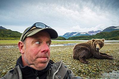 Photographer takes a selfie with a Grizzly bear near a salmon spawning stream, Katmai National Park, Southwest Alaska - p442m967045 by Paul Souders