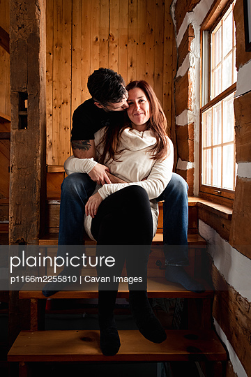 Attractive couple sitting on stairs together inside rustic log cabin. - p1166m2255810 by Cavan Images