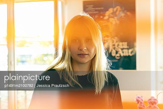 Frau steht in Wohnzimmer und blickt in die Kamera - p1491m2100782 von Jessica Prautzsch