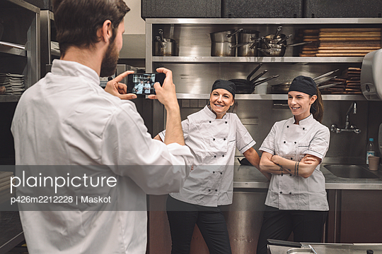 Male chef taking photograph of smiling female coworkers in commercial kitchen - p426m2212228 by Maskot
