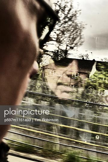 Mann schaut aus dem Zugfenster - p597m1161403 von Tim Robinson