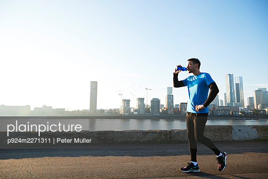 UK, London, Jogger drinking with downtown skyline in background - p924m2271311 by Peter Muller