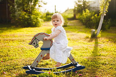 Little girl riding rocking horse in the garden - p1642m2222252 by V-fokuse