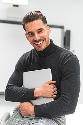Smiling young businessman holding laptop at office - p300m2281934 by Josu Acosta