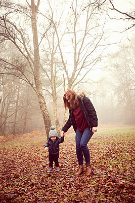 Male toddler holding mother's hand in forest - p429m1407990 by Emma Kim
