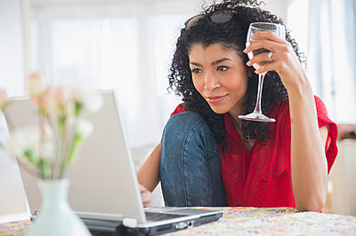Mixed race woman drinking wine and using laptop - p555m1413048 by JGI/Jamie Grill