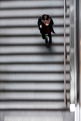 Woman on moving stairs - p739m1109096 by Baertels