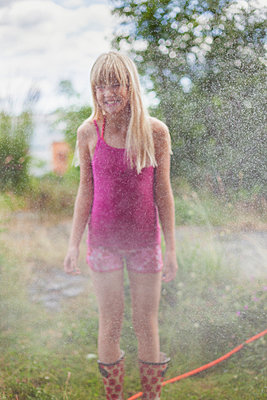 Girl With Long Hair Standing In A Sprinkler In The Garden - p847m888800 by Bildhuset