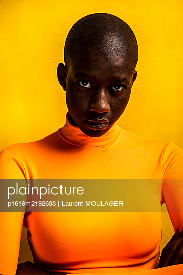 Portrait of a young shaved black girl wearing an orange turtelneck in front of a yellow background - p1619m2192688 by Laurent MOULAGER