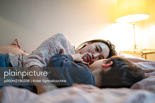 Mother and little son lying together on bed having fun - p300m2180338 by Kniel Synnatzschke