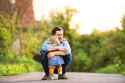 Father hugging little boy on field path - p300m1505842 by HalfPoint