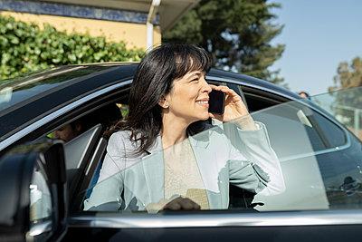 Smiling mature businesswoman talking on mobile phone - p300m2282005 by Jose Carlos Ichiro