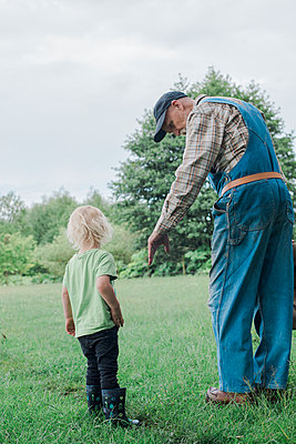 Grandparent with grandson in meadow - p312m1570487 by Rebecca Wallin