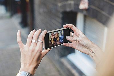 Man kissing woman as she takes selfie through smart phone - p426m1442705 by Maskot