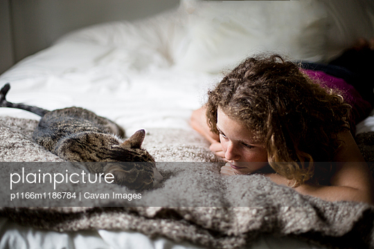 Woman looking at cat while lying on bed at home