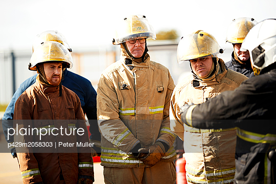 Firemen training, firemen listening to supervisor at training facility - p429m2058303 by Peter Muller