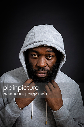 Black man with a sweat shirt facing camera - p590m2092886 by Philippe Dureuil