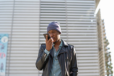 young african man in the city talking on his smartphone - p1166m2218241 by Cavan Images