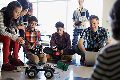 Teachers and pre-adolescent students programming robotics in classroom - p1192m1231029 by Hero Images