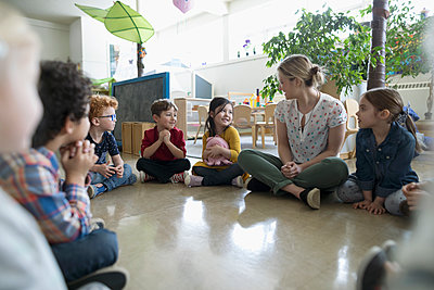 Preschool teacher and students sitting in circle on floor in classroom - p1192m1560186 by Hero Images
