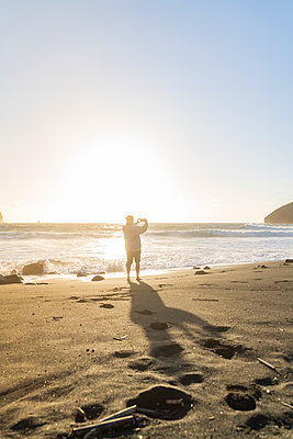 Man standing on the beach at sunset taking pictures, Sao Miguel Island, Azores, Portugal - p300m2169881 by VITTA GALLERY