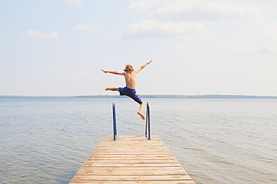Boy jumping off end of dock on Balsam Lake; Ontario, Canada - p442m1086637 by Vast Photography