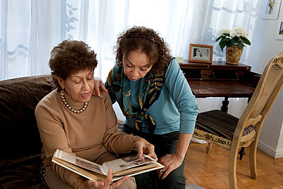 Hispanic mother and daughter looking at photo album - p555m1408857 by Shestock