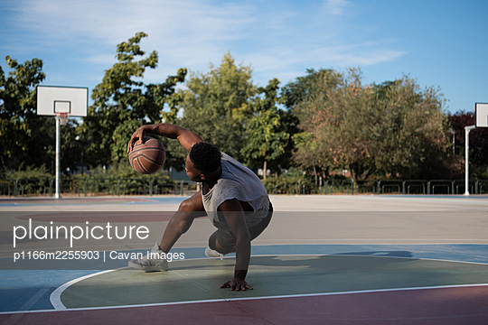 Muscular African American player doing freestyle dribbling on court - p1166m2255903 by Cavan Images