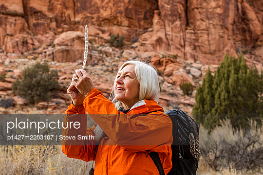 USA, Utah, Escalante, Woman looking at feather while hiking in Grand Staircase-Escalante National Monument - p1427m2283107 by Steve Smith