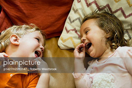 Male and female toddler friends giggling on sofa - p1427m2283147 by Roberto Westbrook