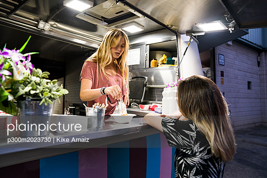 Young woman in a food truck serving customer - p300m2023730 von Kike Arnaiz