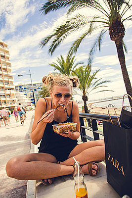 Woman eating at the beach after shopping trip - p1084m986879 by Operation XZ