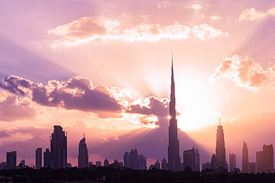 Silhouette Burj Khalifa and skyscrapers against cloudy sky during sunset - p1166m1414749 by Cavan Images