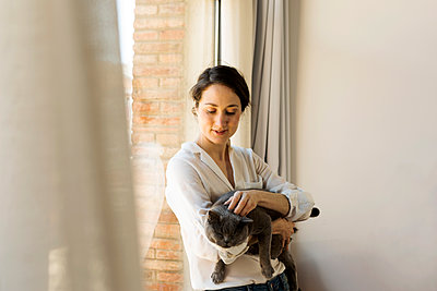Smiling woman with cat on her arms by the window - p1166m2096388 by Cavan Images