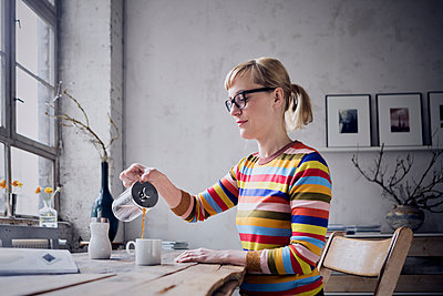 Woman pouring coffee in a mug at desk in a loft - p300m2030210 by Rainer Berg