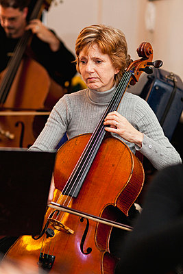 Cello player practicing with group - p429m712175f by Hybrid Images