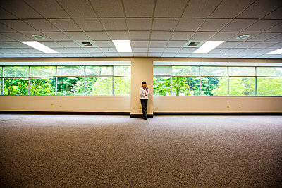 Japanese businesswoman leaning on wall of empty office - p555m1304449 by Jed Share/Kaoru Share