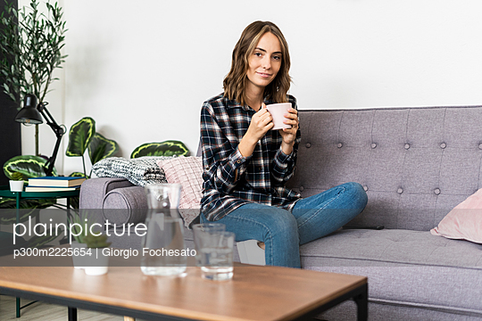 Young woman drinking coffee while sitting on sofa at home - p300m2225654 by Giorgio Fochesato