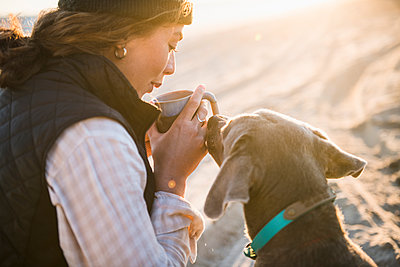 Young woman enjoying drink in mug while beach car camping with dog - p1166m2285582 by Cavan Images