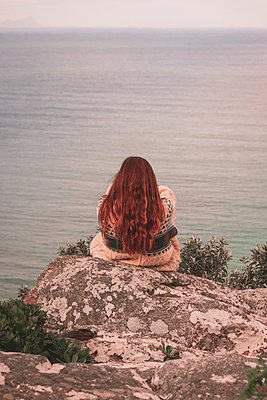 Red-haired woman on rocky coast, view onto the sea - p1640m2246196 by Holly & John