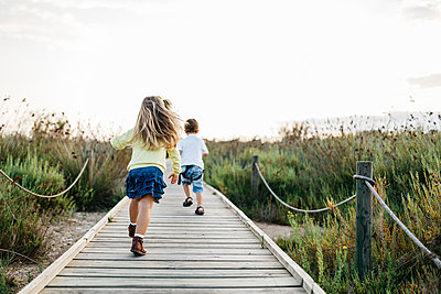 Back view of two little children playing together on boardwalk in nature - p300m1189611 by Josep Rovirosa