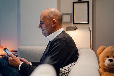 Senior man sitting on couch, reading book - p300m1587086 von Gustafsson