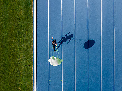 Top view of female runner with parachute on tartan track - p300m2132490 by Stefan Schurr