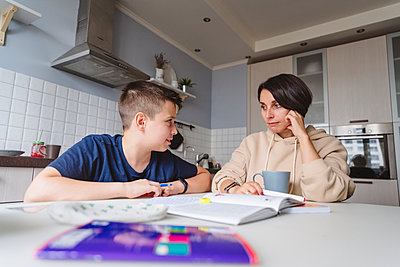 Mother and son looking at each other while studying in kitchen at home - p300m2277689 by Katharina und Ekaterina